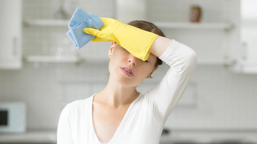 Mujer cansada limpiando la casa