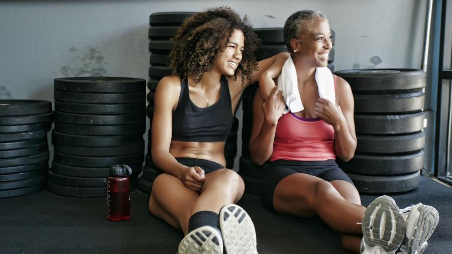 Mujer joven y su mamá sentadas en el piso del gym