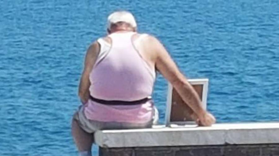 Hombre anciano mirando al mar con la foto de su esposa