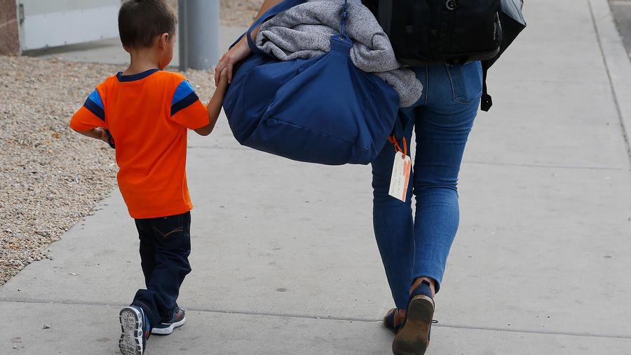 Una madre indocumentada camina con su hijo después de meses separados