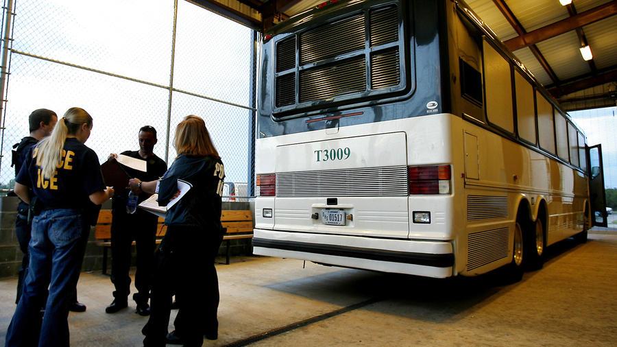 Agentes del ICE junto a un autobús en una foto de archivo