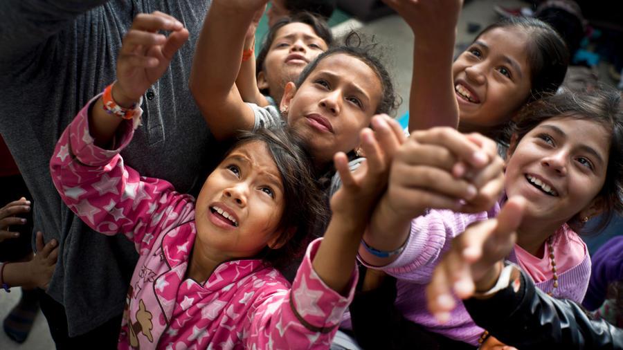 Niños de la caravana migrante en Tijuana recogen caramelos que les ofrece un trabajador social
