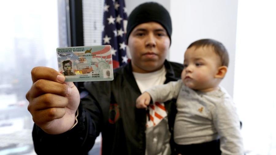 Luis Escamilla muestra su tarjeta de residente mientras carga a su hijo Jayden