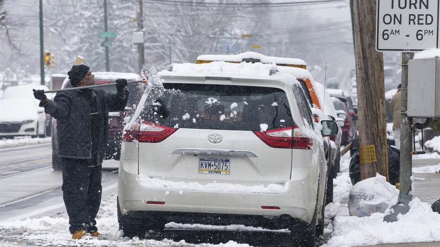Un hombre limpia la nieve de su carro