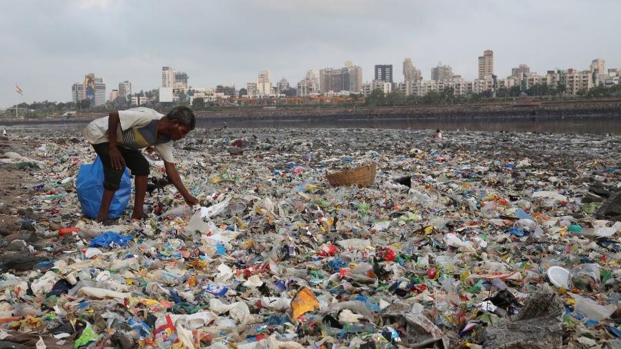 En esta foto del 4 de junio de 2018, un hombre recolecta plástico en la orilla del Mar Arábigo, lleno de bolsas de plástico y otra basura, en Mumbai, India.