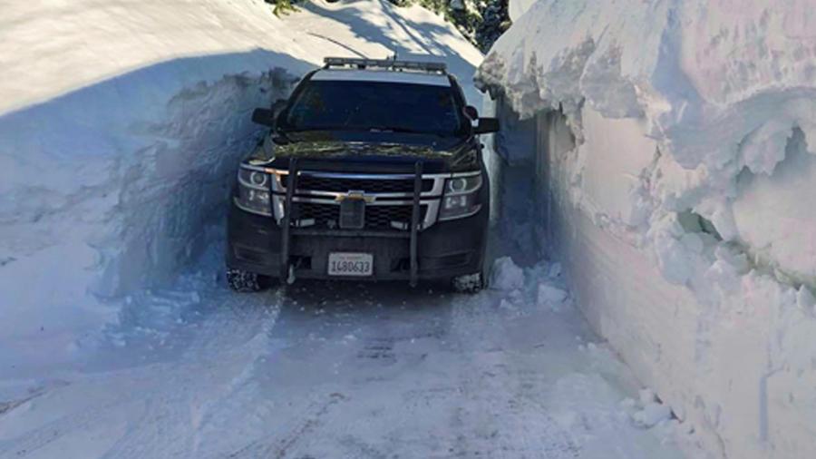 Un vehículo pasando entre montículos de nieve en una imagen de archivo