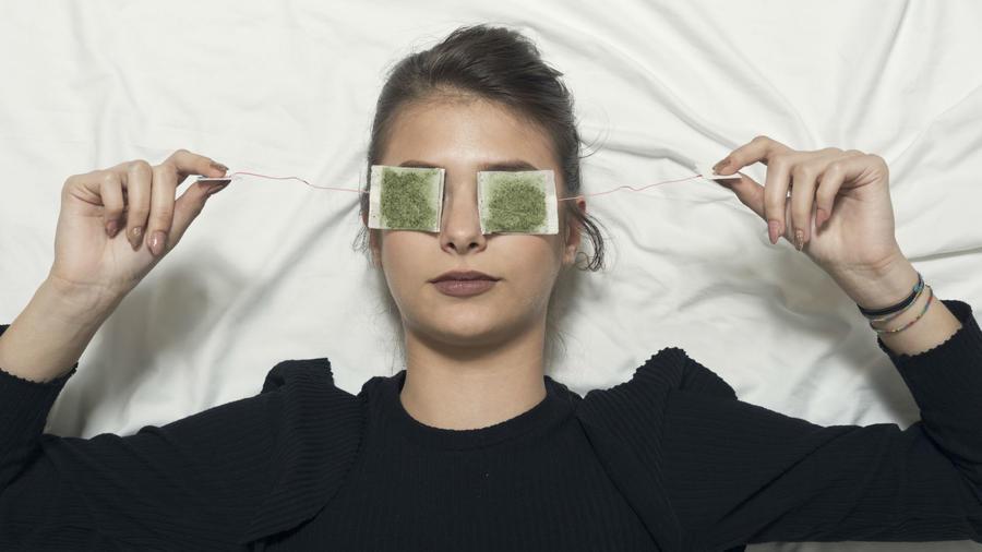 Mujer con bolsas de té sobre los ojos