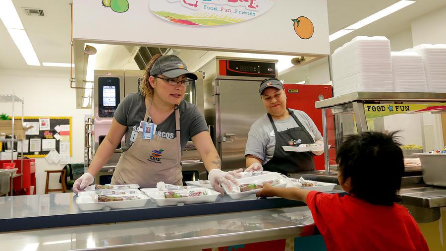 Un niño recibe comida en la cafetería escolar