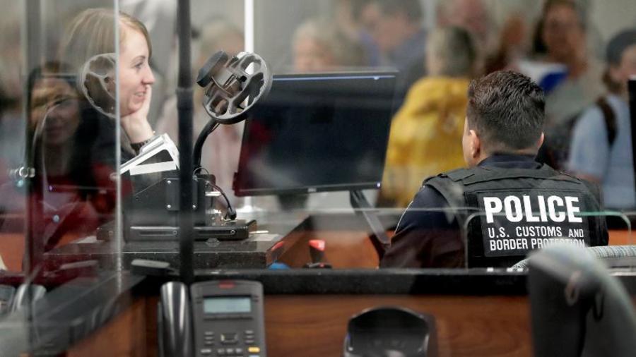 Un agente de Aduanas y Protección Fronteriza examina a un pasajero con un escaneo facial en una imagen de archivo.