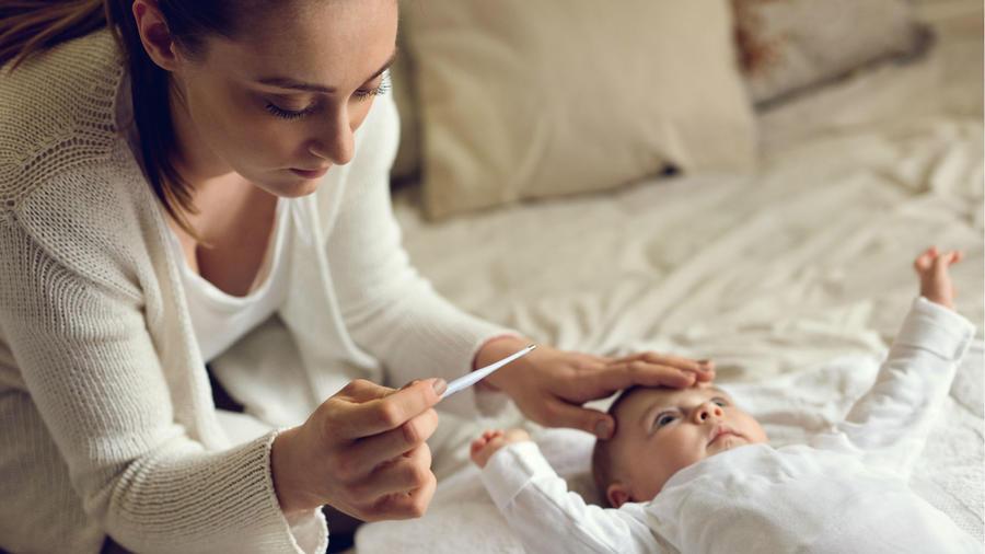 Madre tomando la temperatura a su bebé