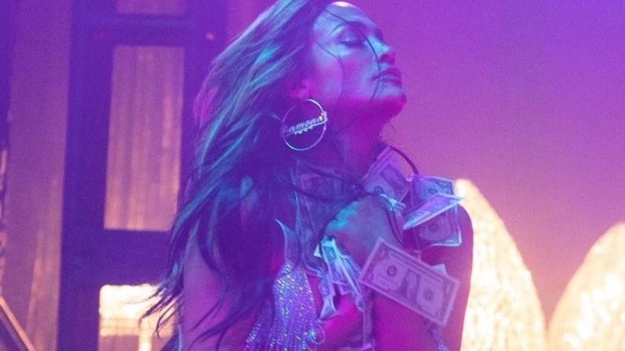 Jennifer Lopez abrazando un montón de dolares
