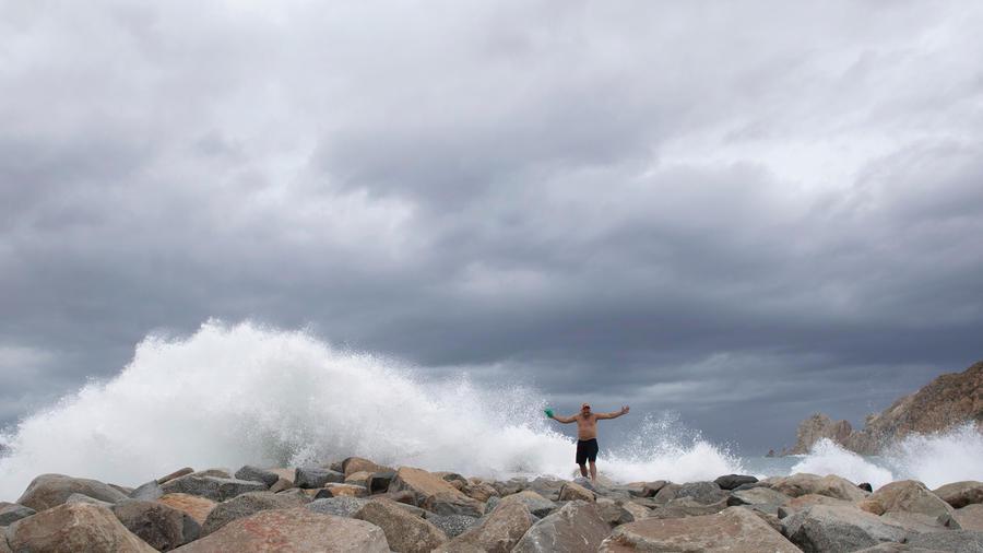 Una persona en la playa en Baja California ante las olas embravecidas por la llegada de Lorena