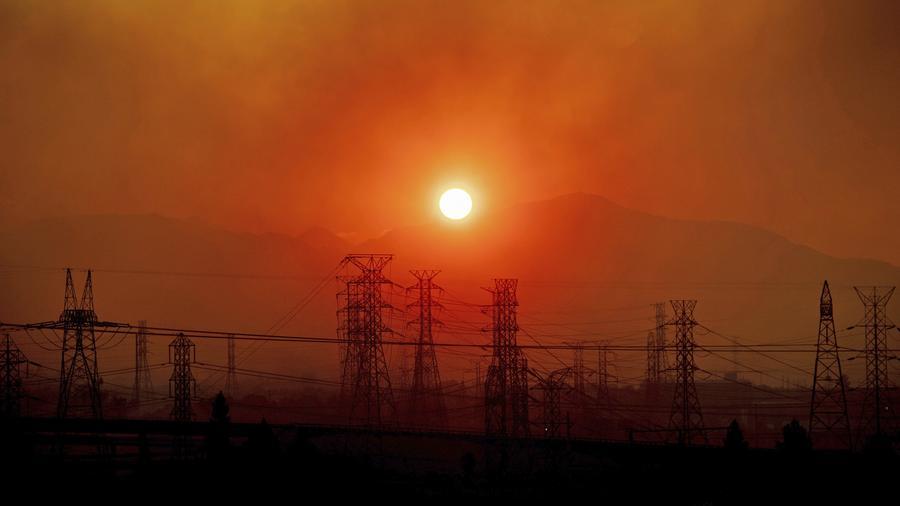 El humo del incendio forestal de Saddle Ridge se cierne sobre las líneas eléctricas cuando sale el sol en Newhall, California