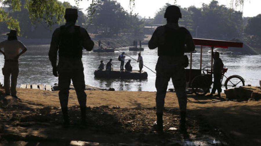 Integrantes de la Guardia Nacional vigilan a migrantes en el río Suchiate