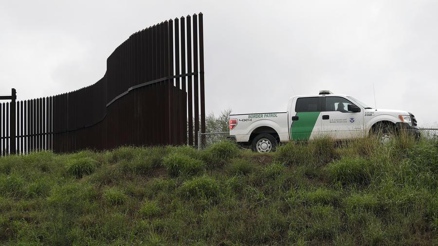 Un vehículo de la Oficina de Aduanas y Protección Fronteriza, junto a una sección del muro, en Hidalgo, Texas.