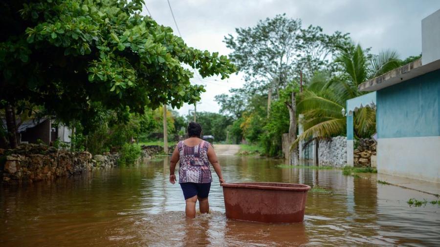 Una mujer en México camina en medio de las inundaciones causadas por la tormenta tropical CristóbalTecoh, cerca de Mérida, Mexico, este 3 de junio.