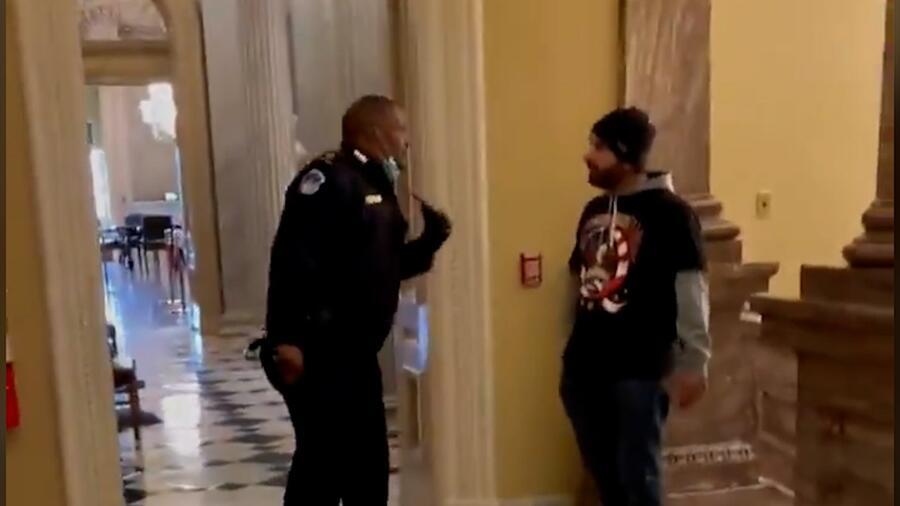 Eugene Goodman frente a uno de los agresores del Capitolio en el video captado por el reportero Igor Bobic del HuffPost. A la izquierda, donde se ven sillas, está la entrada a la cámara del Senado.