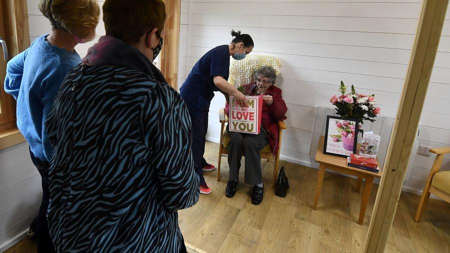 Carmel Matthews y Rita Ray visitaron a su mamá, Rosalyn Redmond, de 92 años, y le hablaron a través de una pantalla protectora para prevenir el COVID-19, en una residencia de ancianos en Dublín, Irlanda, el 14 de marzo del 2021.
