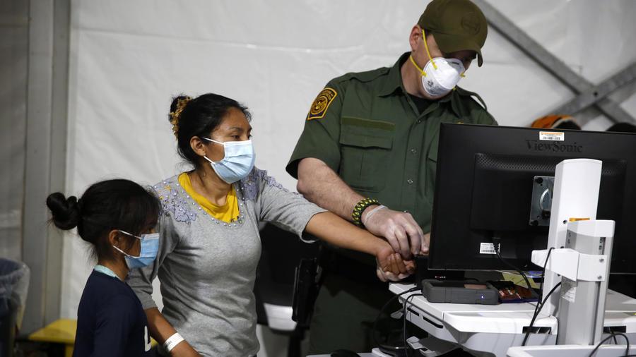 Se toman las huellas digitales de una migrante en el área de admisión en las instalaciones de detención del Departamento de Seguridad Nacional el 30 de marzo de 2021 en Donna, Texas.