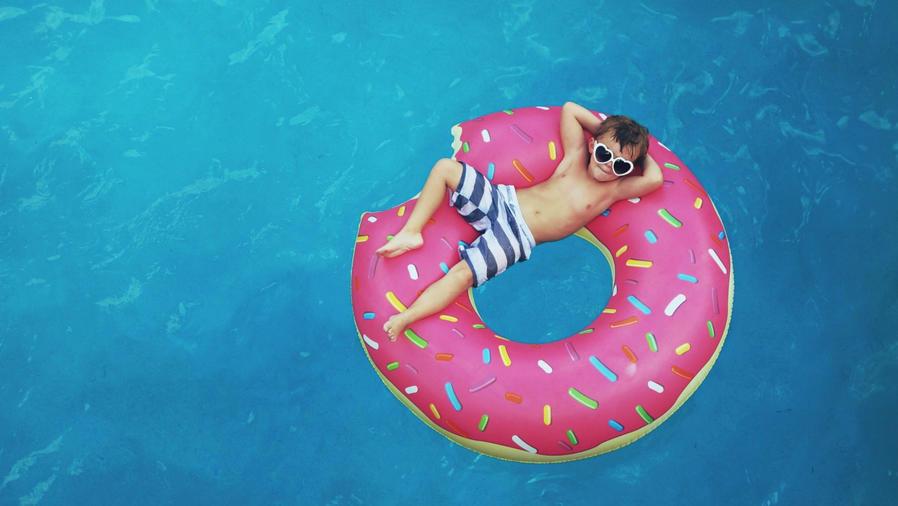 Niño recostado sobre un flotador de dona en la piscina