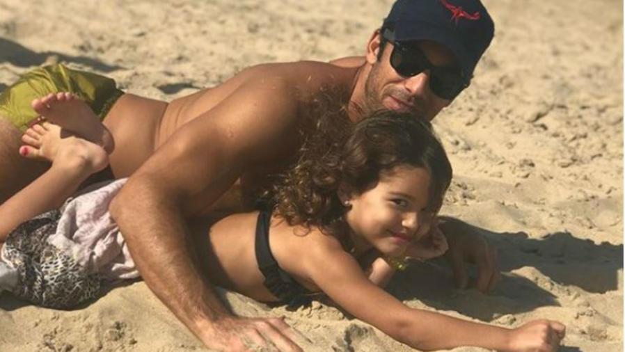 Aarón Díaz jugando con su hija en la playa