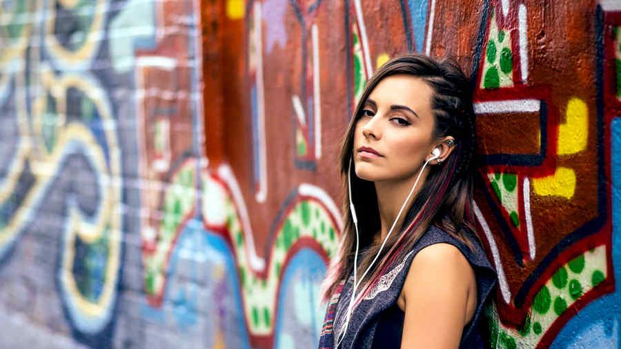 """María Elisa Camargo en un callejón con graffiti en """"Bajo el mismo cielo"""""""