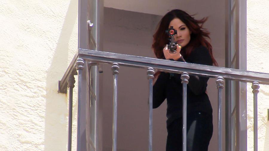 Cynthia Olavarría disparando un arma desde un balcón en Tierra de Reyes