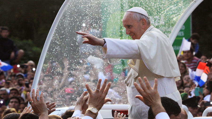 "Pope Francis waves to a crowd of faithful after making a brief stop outside the women's jail ""Good Pastor"" (Buen Pastor) where a choir of inmates sang to him, in Asuncion"