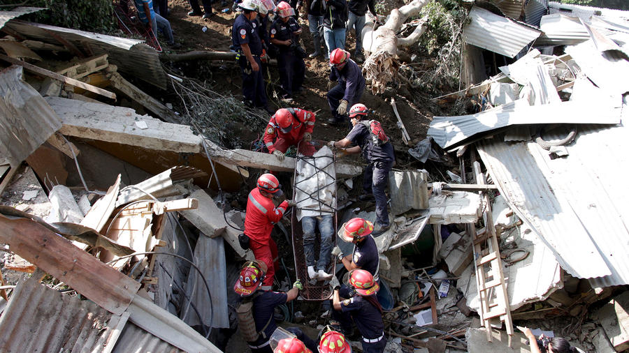 Rescue team members retrieve the body of a landslide victim in Santa Catarina Pinula, on the outskirts of Guatemala City