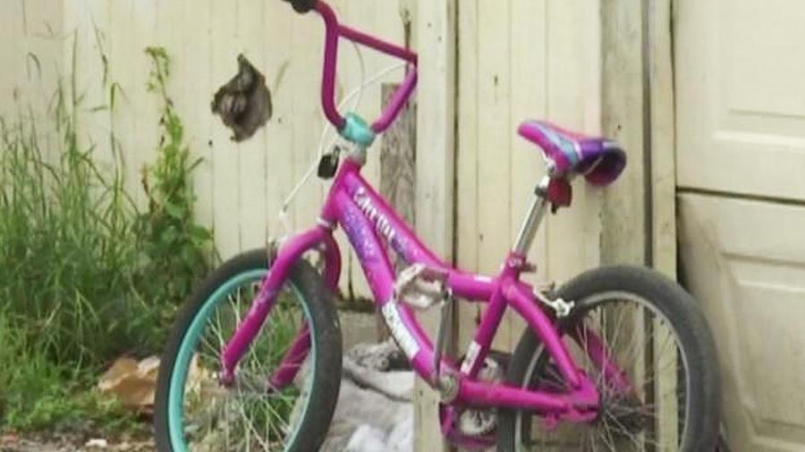 bicicleta rosa recargada en puerta