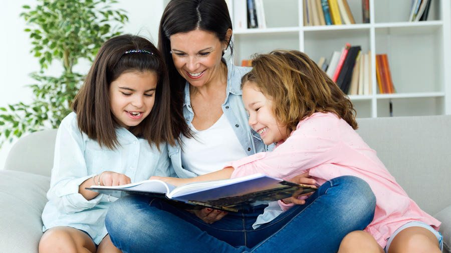 mujer leyendo con sus hijas