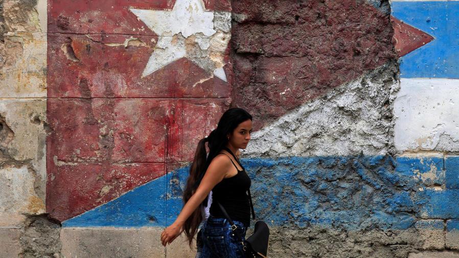 mujer cubana pasa frente a bandera