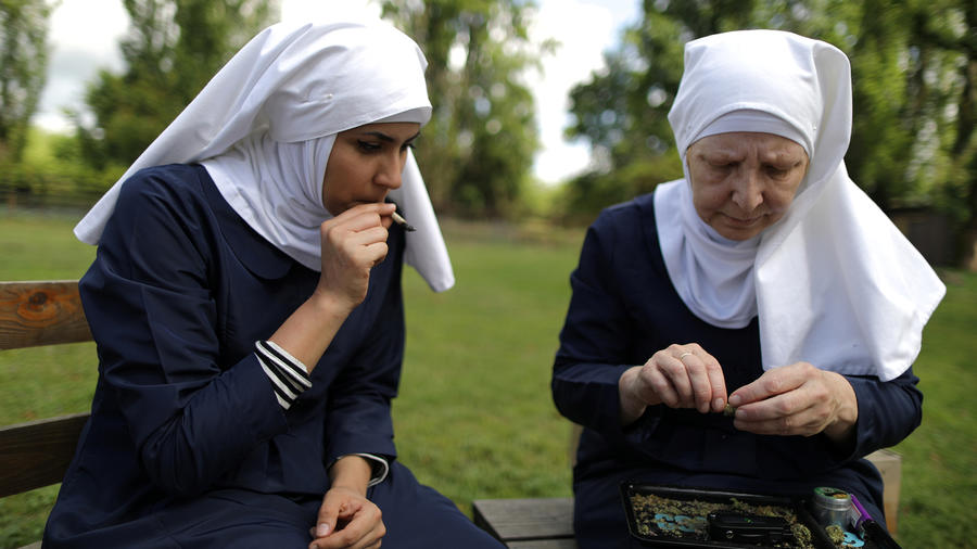 """California """"weed nun"""" Christine Meeusen, and India Delgado, who goes by the name Sister Eevee, smoke a joint at Sisters of the Valley near Merced"""