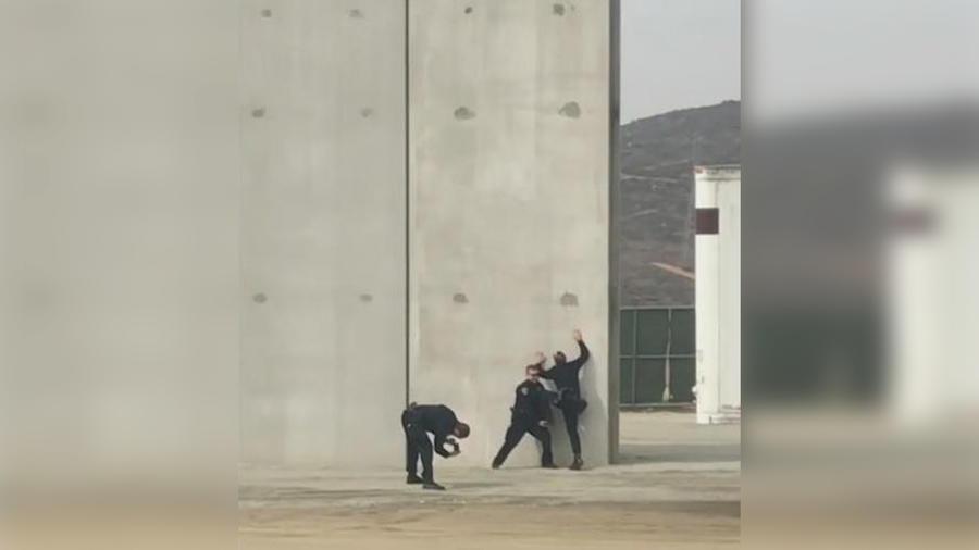 Captan a policías posando frente al muro fronterizo como inmigrantes queriendo cruzar