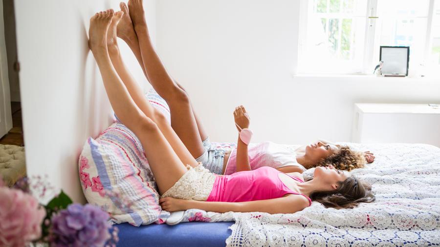 Mujeres con las piernas en la pared.