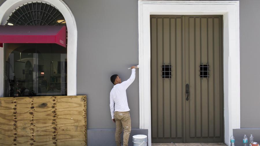 Un hombre pinta el  marco de una puerta que fue dañado durante las protestas en Puerto Rico.