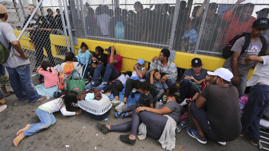 Migrants gather next to the border fence after camping out on the Gateway International Bridge that connects downtown Matamoros, Mexico with Brownsville.