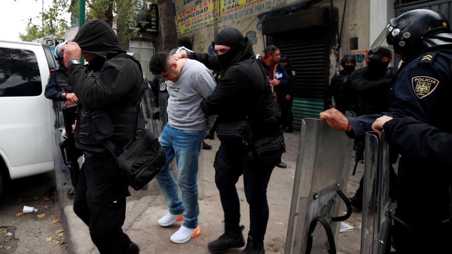 Policías junto a uno de los 31 detenidos durante un operativo contra el cártel de Tepito en Ciudad de México el 22 de octubre de 2019