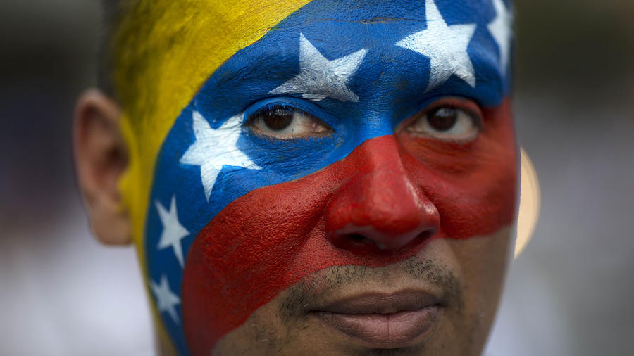 Un hombre con la cara pintada con la bandera de Venezuela.
