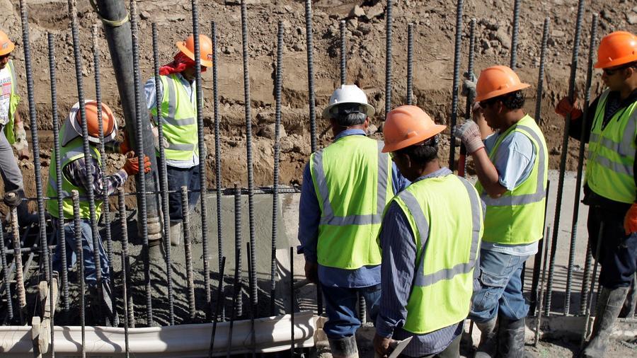 Los trabajadores trabajan para completar la construcción del muro fronterizo en Granjeno, Texas