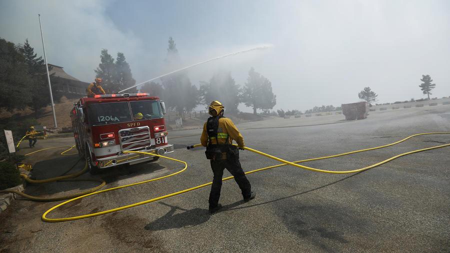 Los bomberos rocían agua mientras que un helicóptero se acerque para reponer los suministros de agua mientras defienden el observatorio Mount Wilson del incendio Bobcat en Los Ángeles, California, EE.UU.