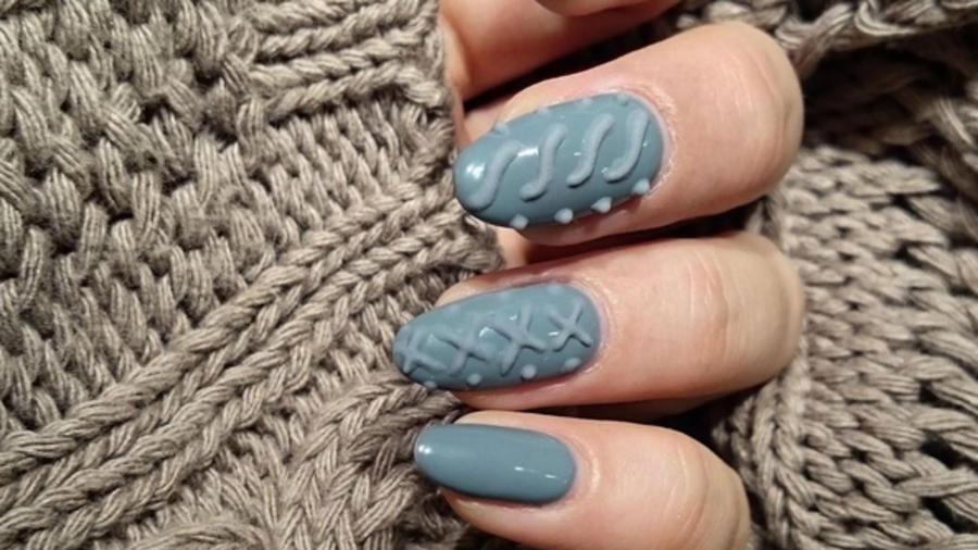 Manicure azul sobre sweater beige