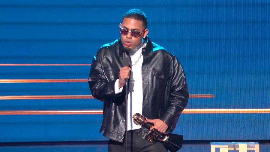 """Myke Towers acepta su premio a """"Nuevo Artista del Año"""" durante los Premios Billbaord 2021 en el Watsco Center de Miami, Florida el 23 de septiembre en el vistiendo una chamarra negra con mangas de cuero, camiseta blanca, gafas de sol negras y zapatos negr"""
