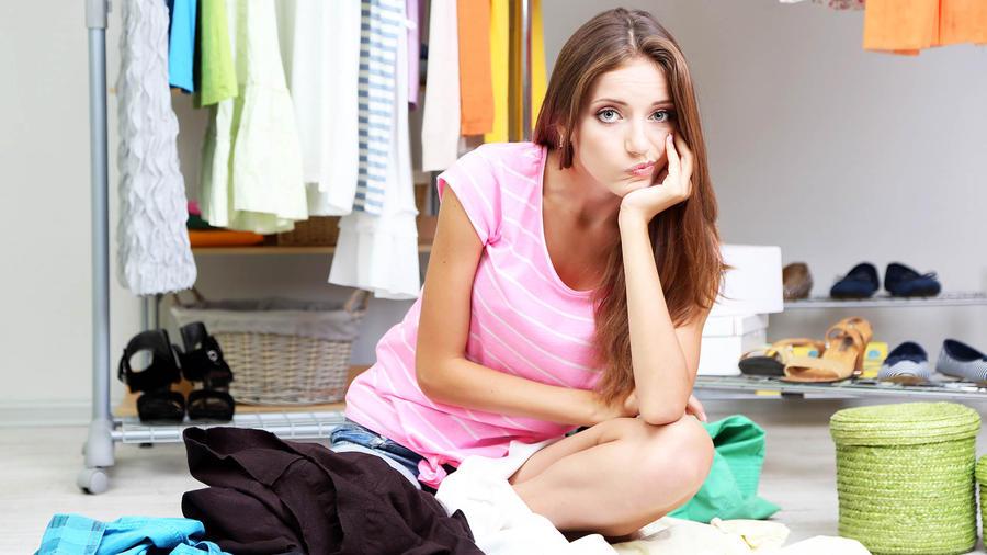 Mujer disgustada sentada en el armario