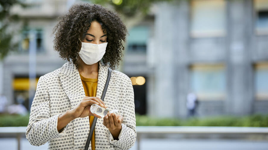 Mujer con mascarilla poniéndose gel antibacterial