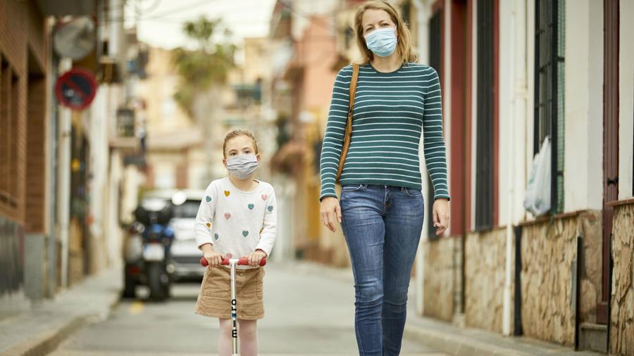 Madre e hija usando máscara facial mientras caminan