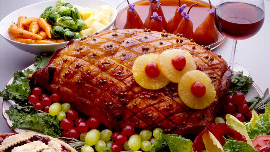 Jamón horneado con frutas y vegetales.