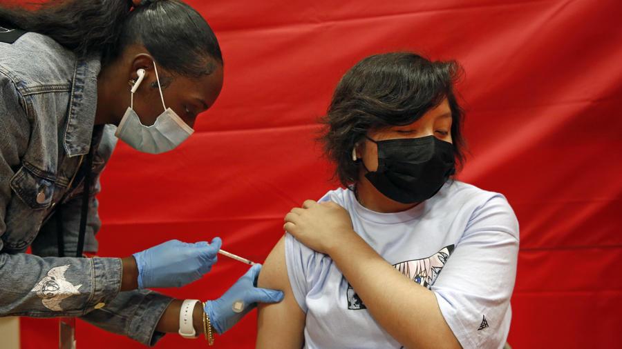 Alex Olvera, de 15 años, recibe la vacuna de Pfizer contra el COVID-19 de la mano de la enfermera Rickeyva Foster, en una escuela de los Ángeles California, el 17 de mayo de 2021.