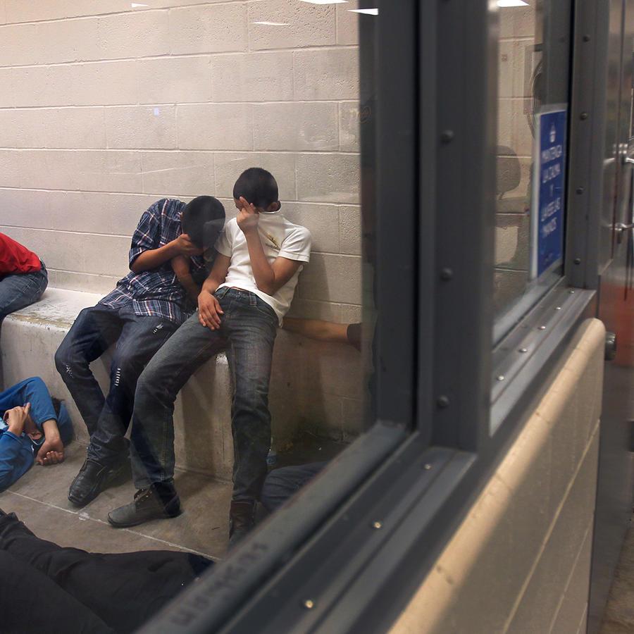 Inmigrantes en centro de detención ocultan su rostro con la mano
