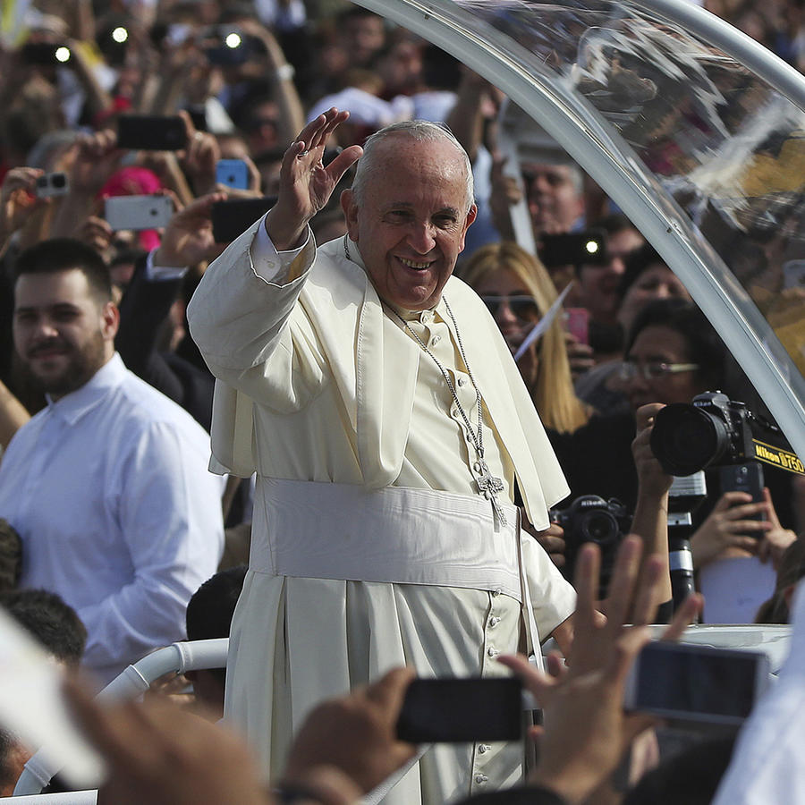 Pope Francis waves as he arrives to lead a mass in Asuncion